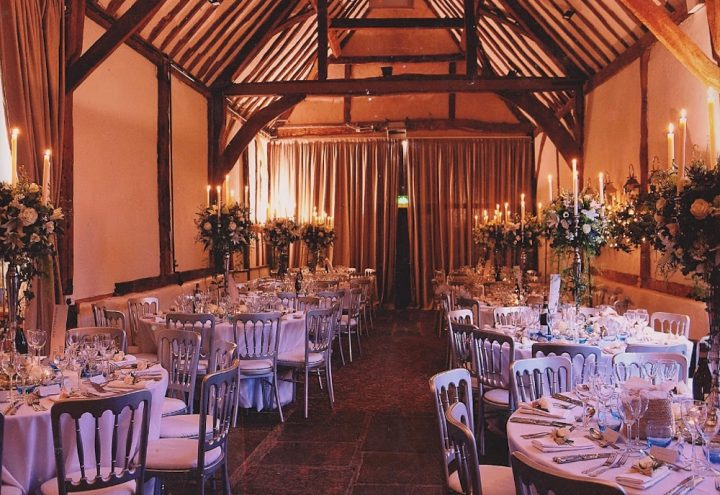 bix manor barn wedding reception white table cloths on round tables silver chairs wood beam ceiling