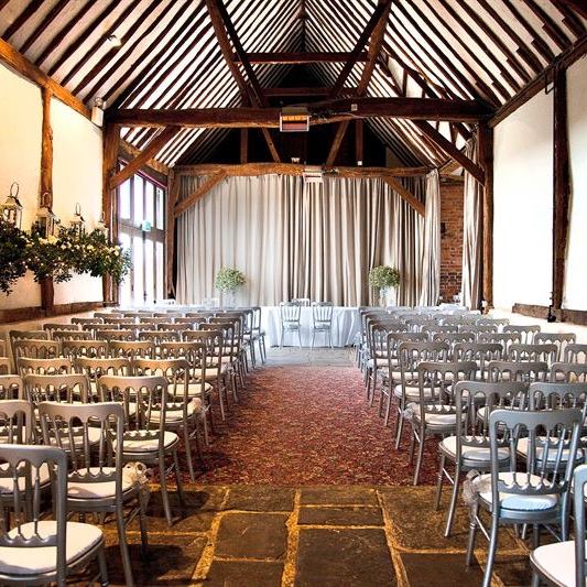 bix manor indoor barn wedding ceremony silver chairs lined up under wood beam ceiling
