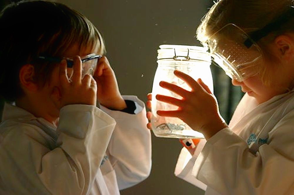 young boy and girl in white lab coats and goggles holding lit up glass jar