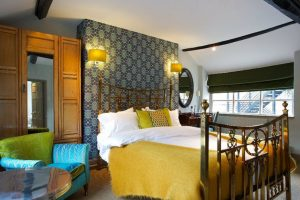 grey feature wall yellow bed sheets on gold metal bed in feathers hotel room