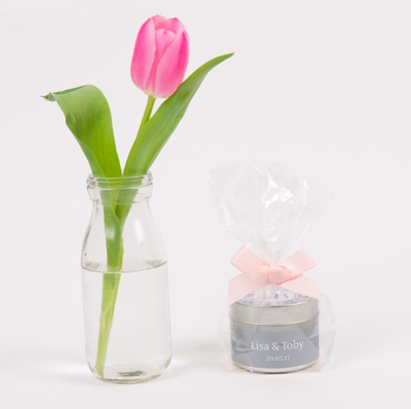 house of bluebell candle wrapped in cellophane tied with a pink bow next to a vase containing single pink tulip