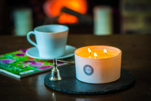 house of bluebell three wick candle on round black slate white mug onto of a magazine