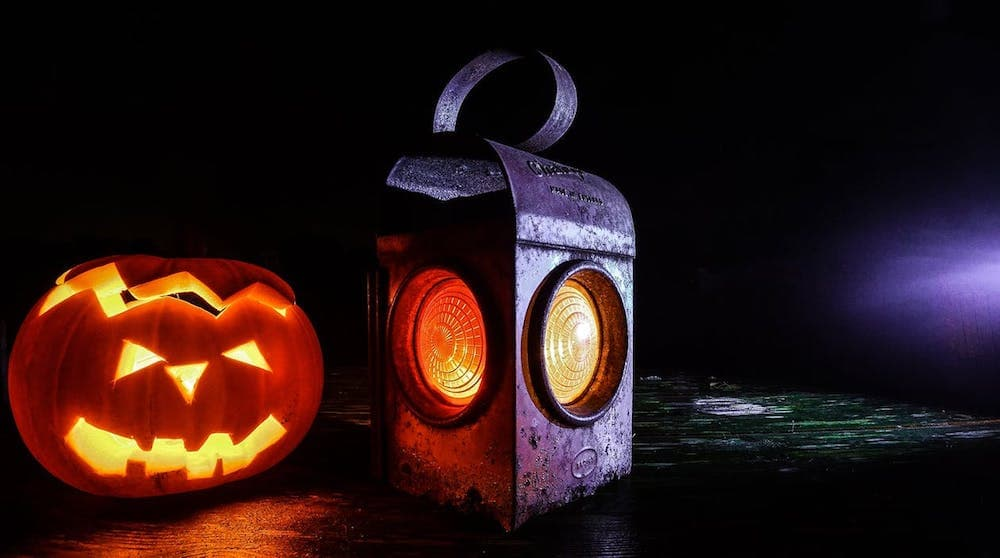 pumpkin with face carved in next to metal lantern