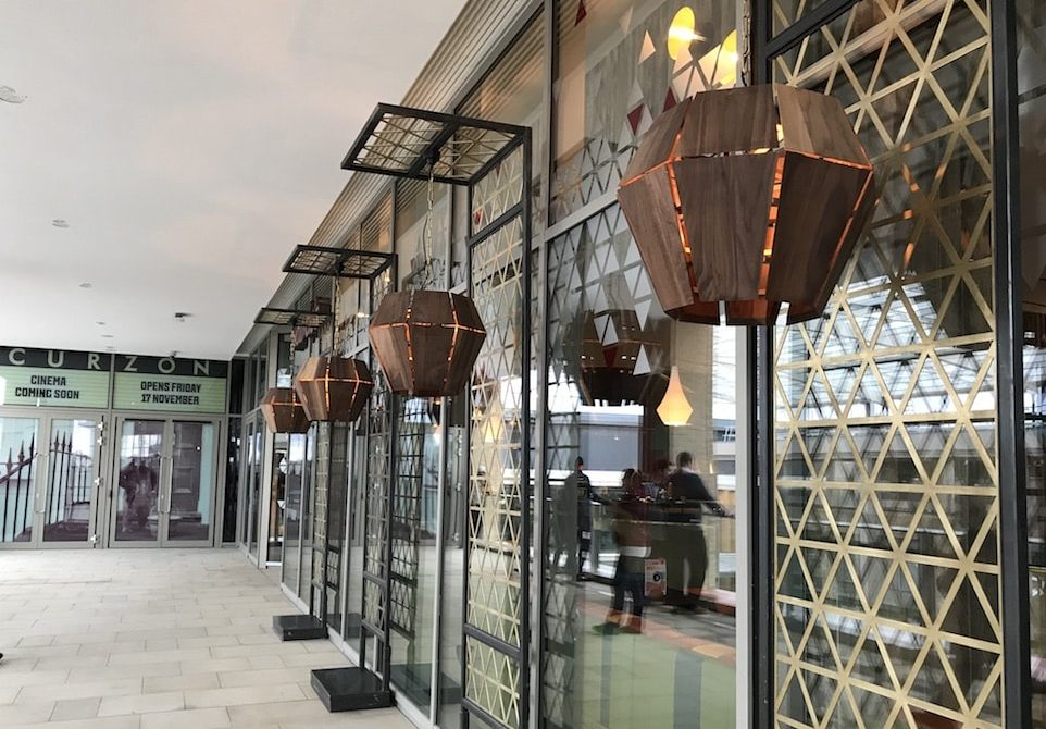 lanterns on a wall with concrete walkway and cinema ahead