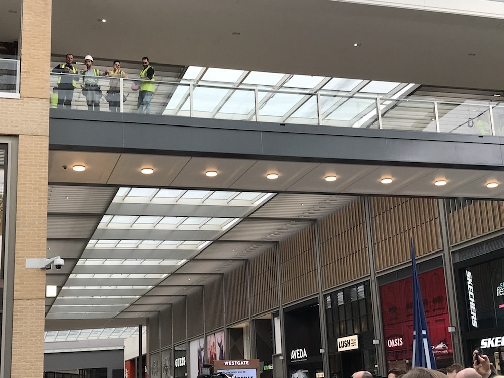 builders watching from a balcony in a shopping centre