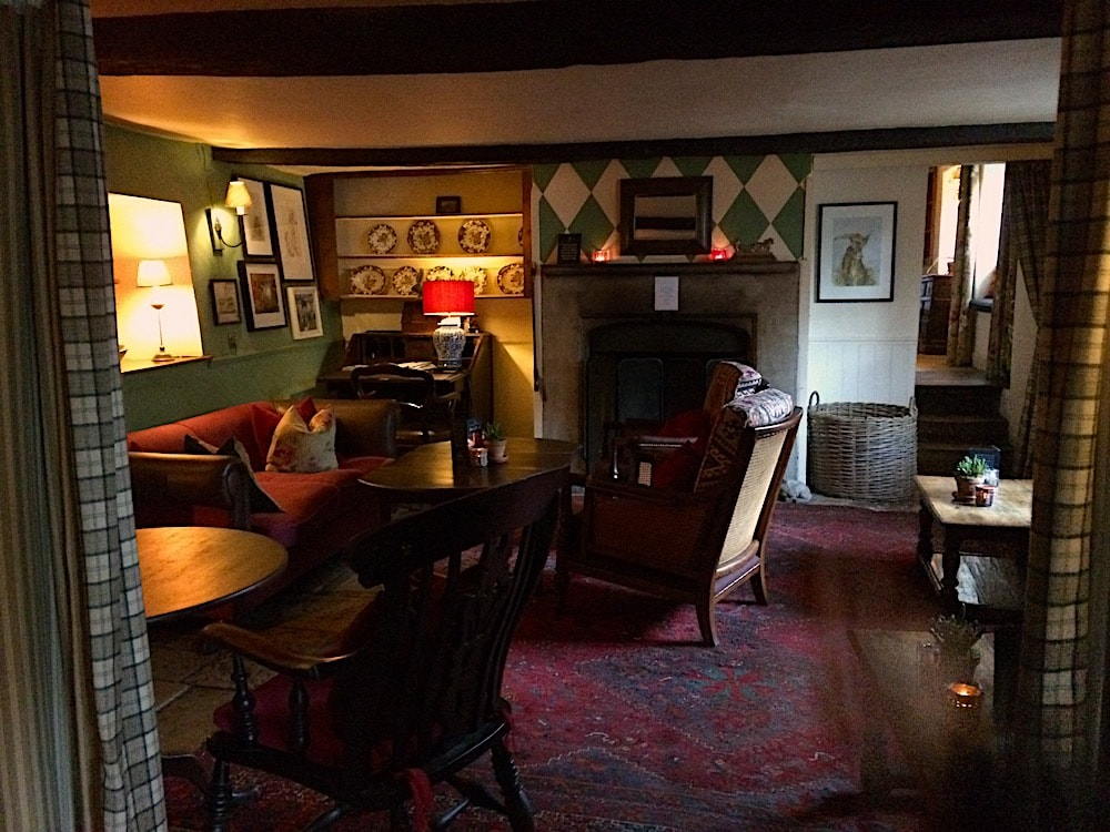old inn interior rugs flagstone floors fireplace pictures on walls tables