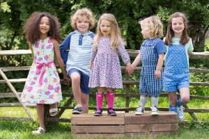 leveret children's clothes children wearing pink dresses blue shorts girls and boys together in nature