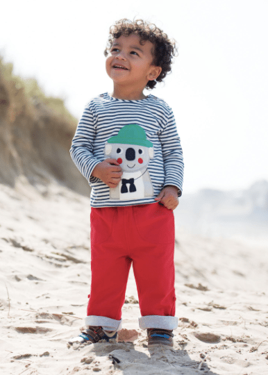 leveret boy smiling in red trousers blue-striped shirt on beach dark hair children's clothes