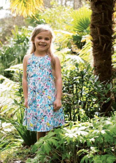 leveret girl smiling in floral blue dress in nature blond hair children's clothes