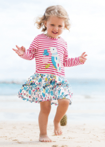 leveret girl smiling in floral blue white skirt red-striped shirt on beach blond hair children's clothes