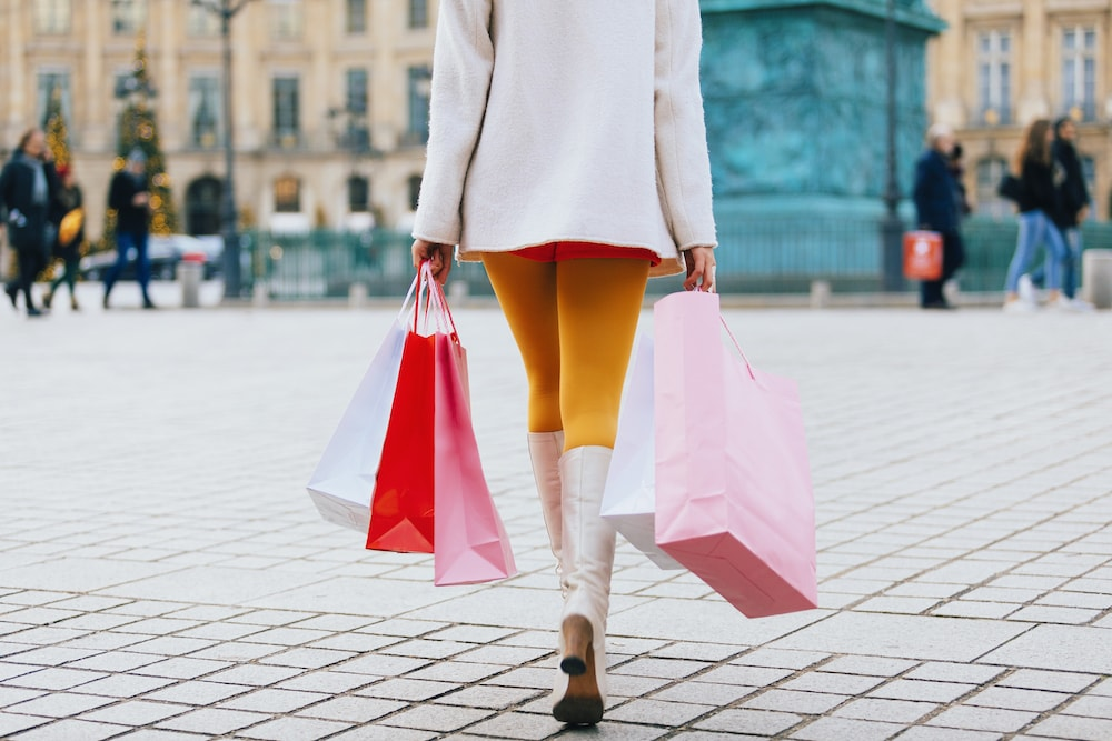woman from behind holding pink red white shopping bags walking on stone pavement wearing yellow leggings white coat white boots