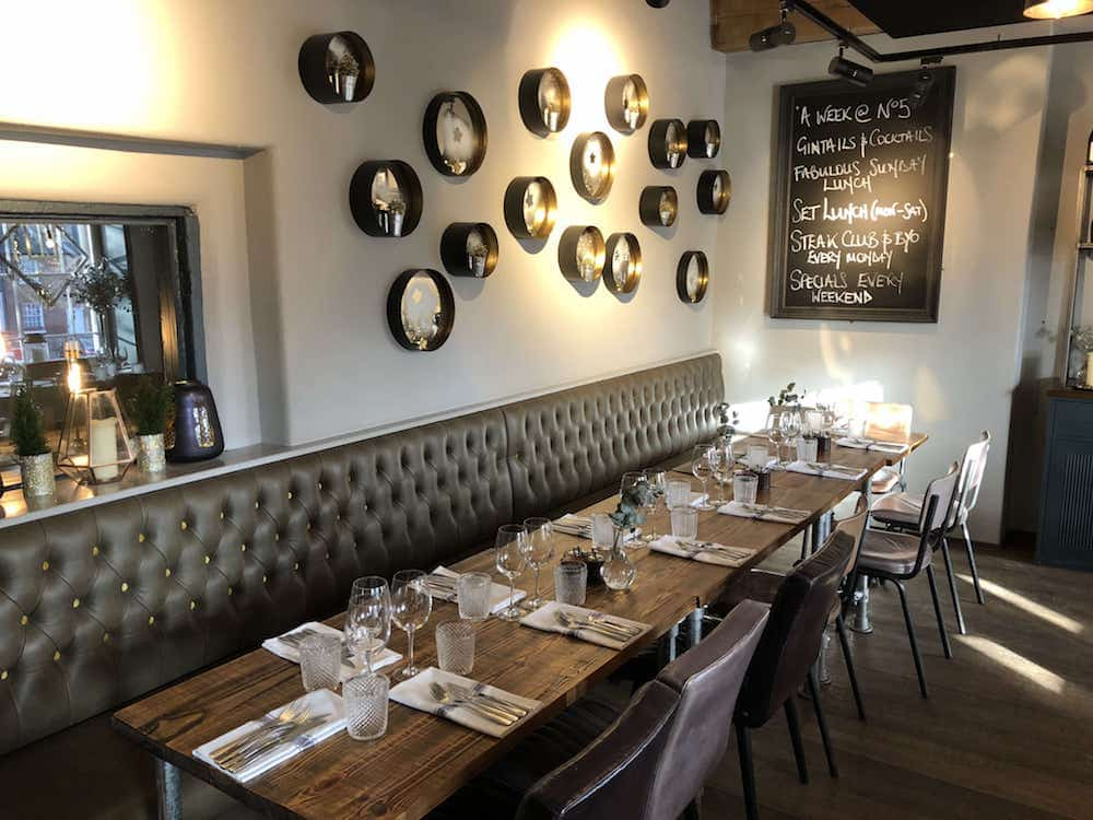 no5 London end restaurant interior white walls silver tins decoration oak table black chair