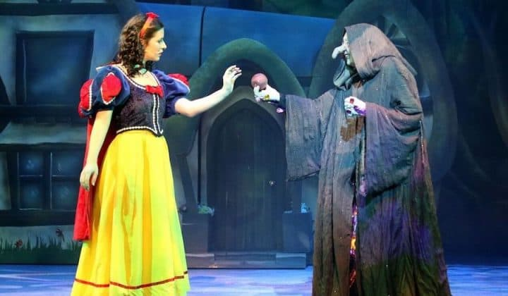 Snow White and seven dwarfs at aylesbury waterside theatre su pollard in black cape handing snow white apple