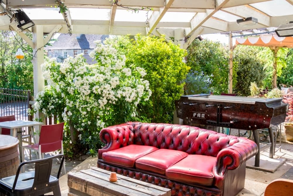 Jacobs inn wolvercote red leather sofa outside amongst big shrubbery