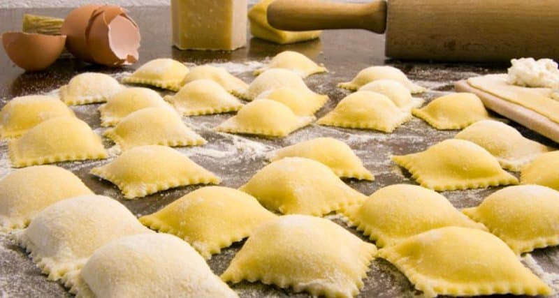 uncooked ravioli pasta on table sprinkled flour