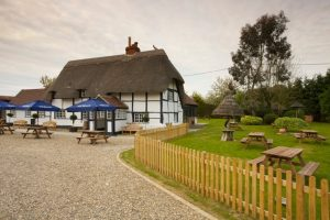 bottle and glass pub exterior thatched roof fenced off grass area