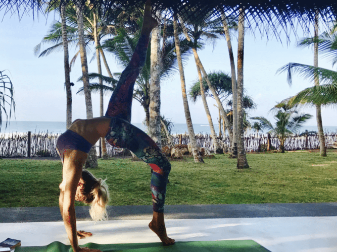 woman in colourful leggings sport bras in backwards crab yoga position palm trees in background