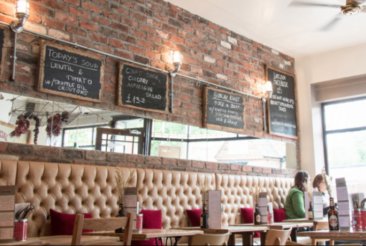 Jacobs Brasserie interior dinning area cream padded headboard pink cushions black chalk boards on brick wall