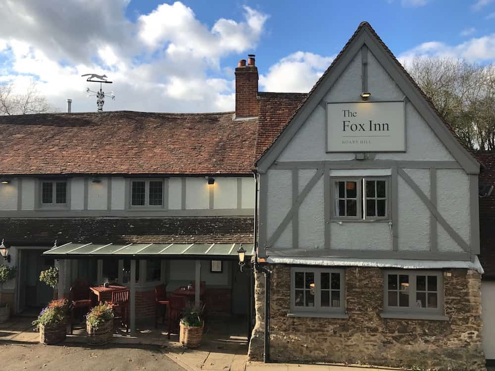 the fox boars hill exterior front building wooden beams stone bottom outdoor dining area