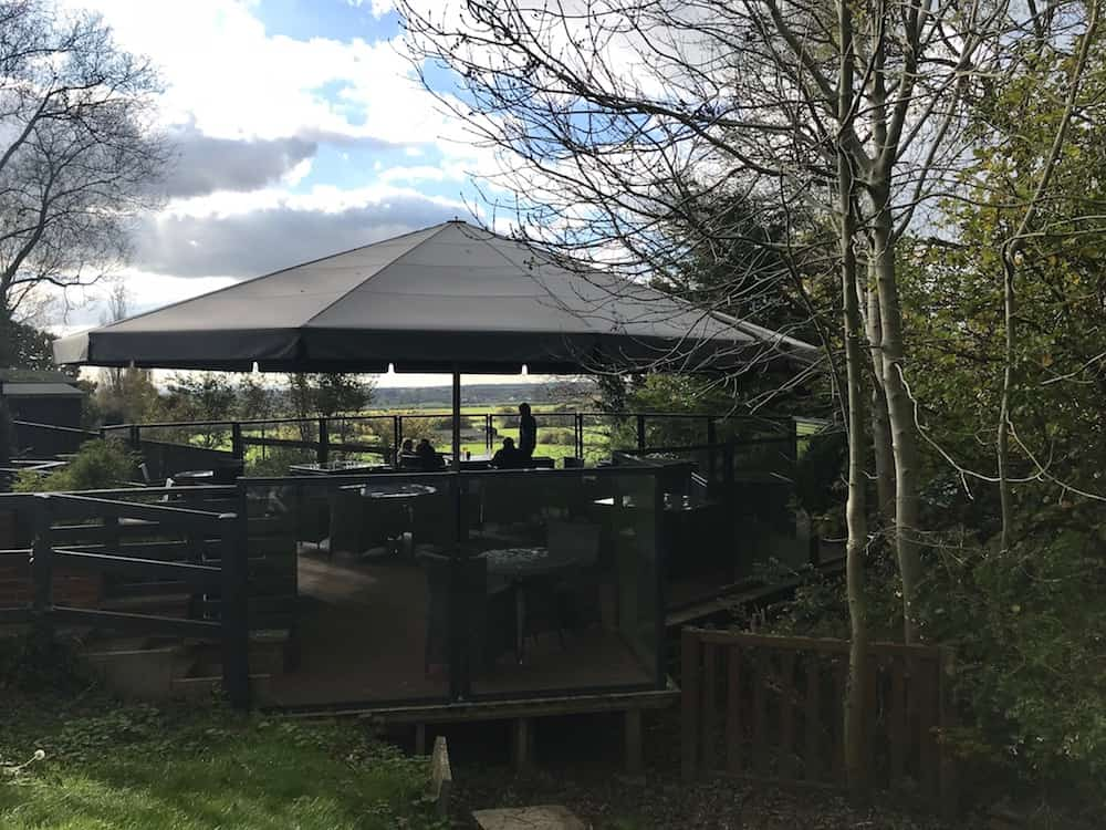 the fox boars hill outdoors parasol dining area surrounded trees