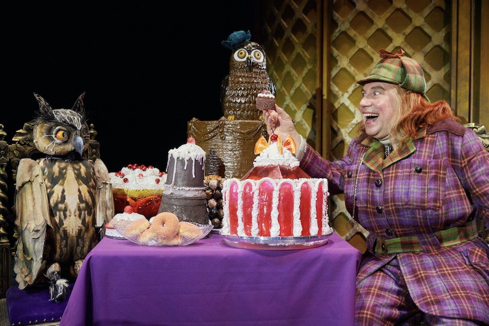 david walliams awful auntie theatre production man dressed as woman at table full of large cakes with owl