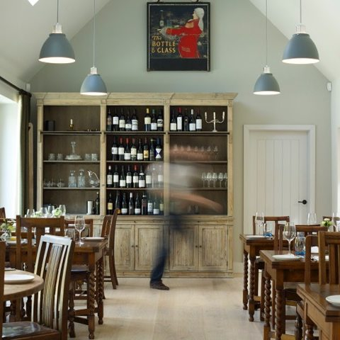 bottle and glass pub dining area mint green walls large cabinet filled with wine bottles wood tables chairs