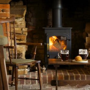 bottle and glass pub brick fireplace old black wood stove wood chair Guinness in pint glass on small table