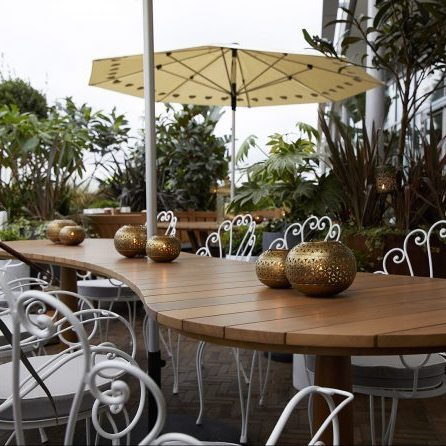 cinnamon kitchen Westgate rooftop terrace wood table white wire chairs yellow umbrella outdoor plants