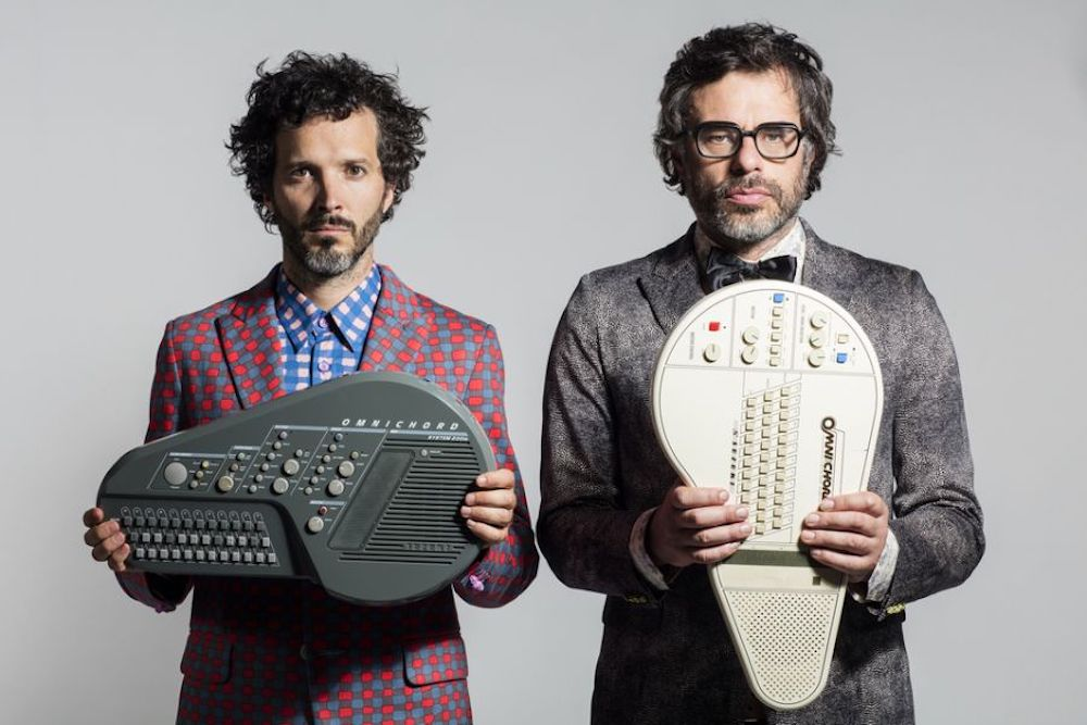 flight of the conchords twopence band holding old musical instruments grey background