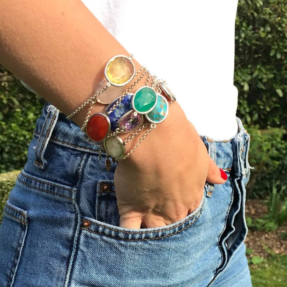 nicky blystad bright coloured gem bracelets stacked on ladies wrist hand in jean pocket
