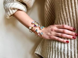 nicky blystad bright coloured gem gold bangles stacked on woman wrist hand on hip being jumper