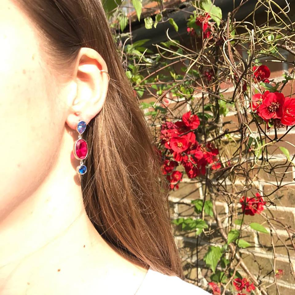 nicky blystad red gemstone earring in ladies ear brunt hair brick wall red flowers background