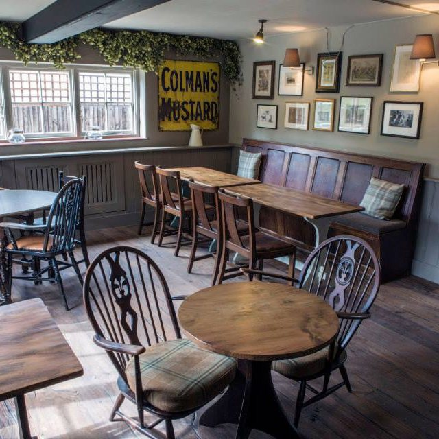 red lion pub dinning area wood floor wood tables chairs wood bench framed pictures on wall colmans mustard sign