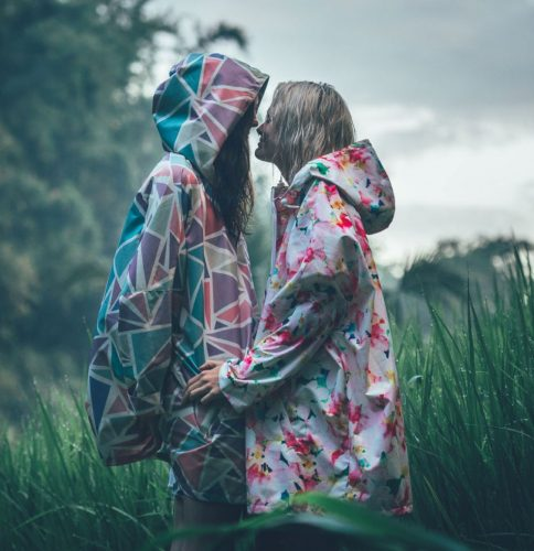 two figures embracing in bright funky coloured white pink green rain coats in front of tall grass and trees