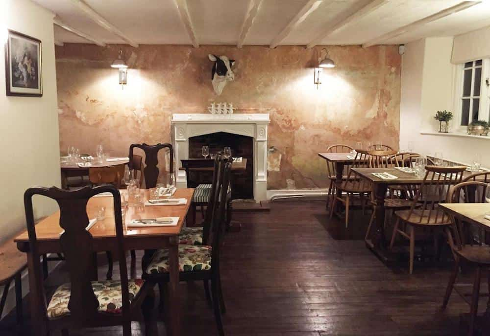 dining room in a pub with cow head on the wall and wooden floor and fireplace