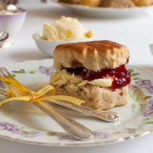 scone on plate with cutlery tied in bow on white table