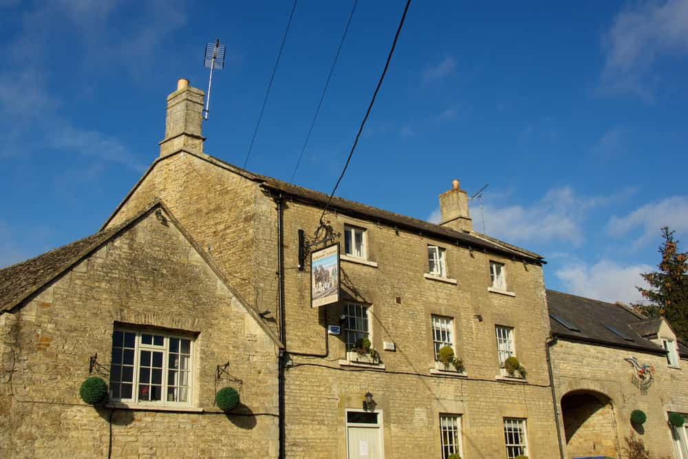 stone three store building with pub sign
