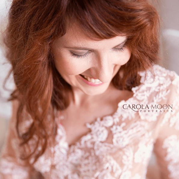 red haired woman laughing looking down white lacey top