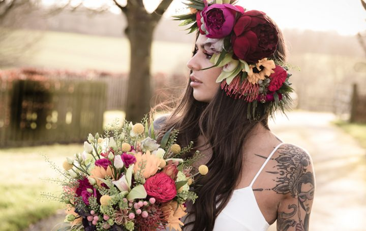 woman looking into distance bright pink purple yellow flowers in long hair in hands outdoor wearing white wedding gown dress