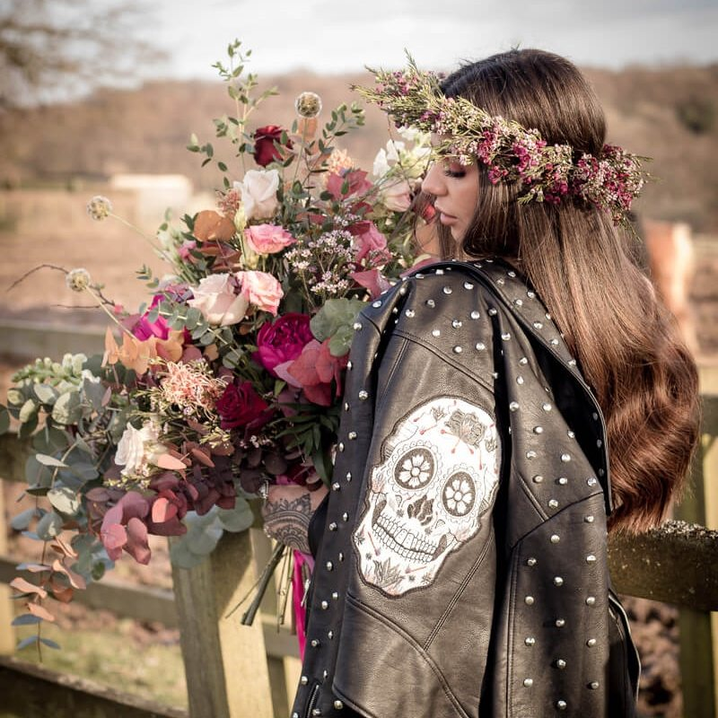 girl holding wild rose bouqet near fence roses in hair skull jacket over shoulder