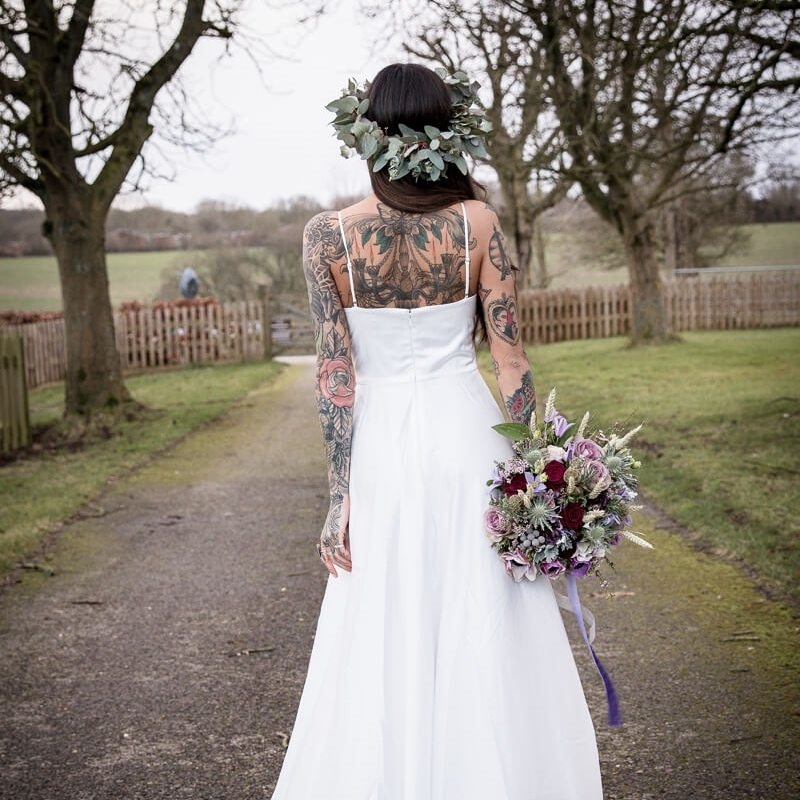 bride in white gown wedding dress tattoos down back arms flowers in hair bouquet in hand