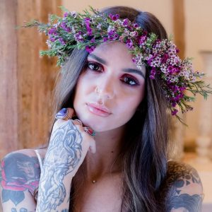 woman staring at camera pink flower crown on head tattoos down arms