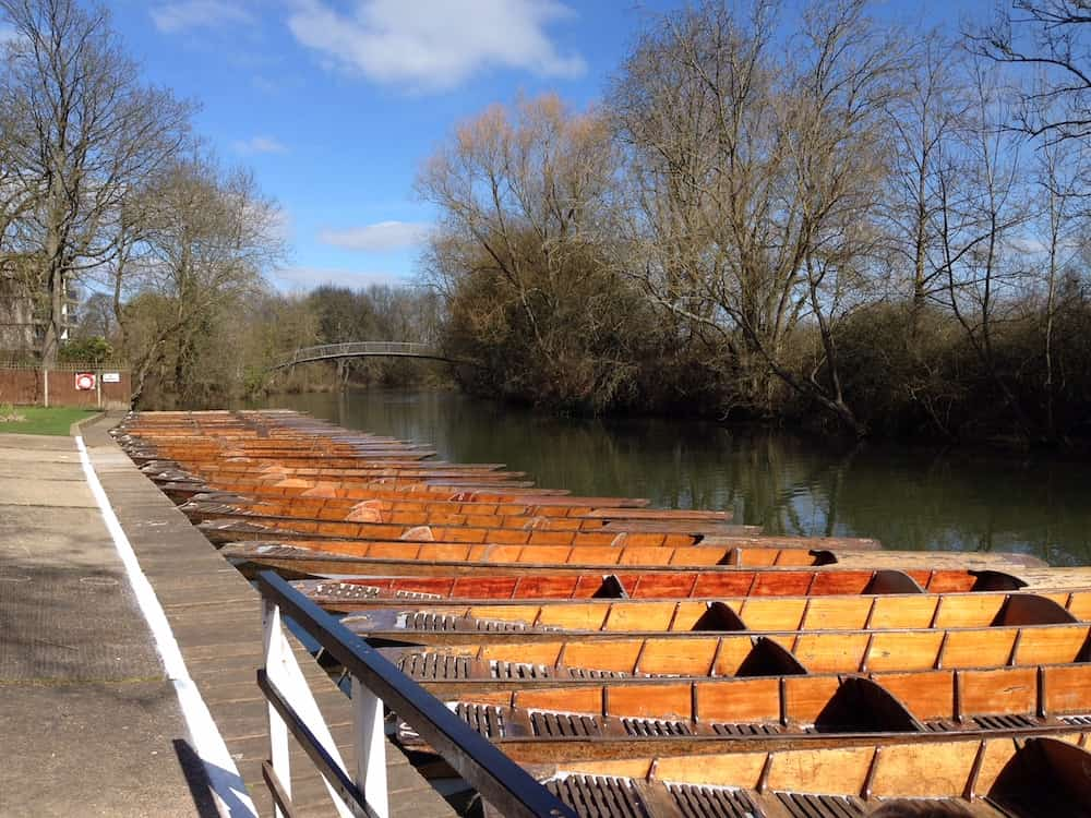 punts in a row on a river in Oxford with blue skies