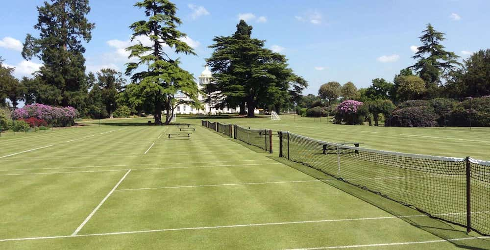 grass tennis courts with blue sky and heritage hotel in the distance