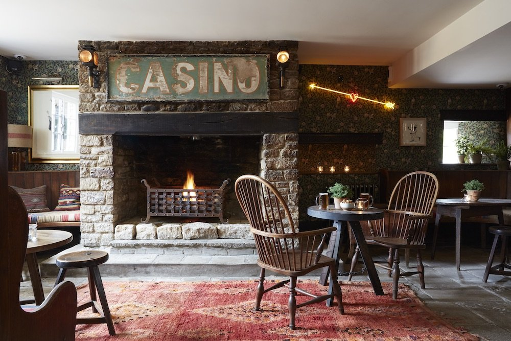Table and chairs in front of open fire
