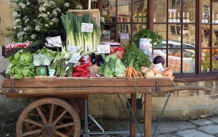 fruit and veg stall outside shop on wooden wheels
