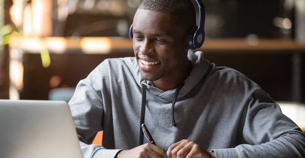 Young man wearing headphone looking laptop
